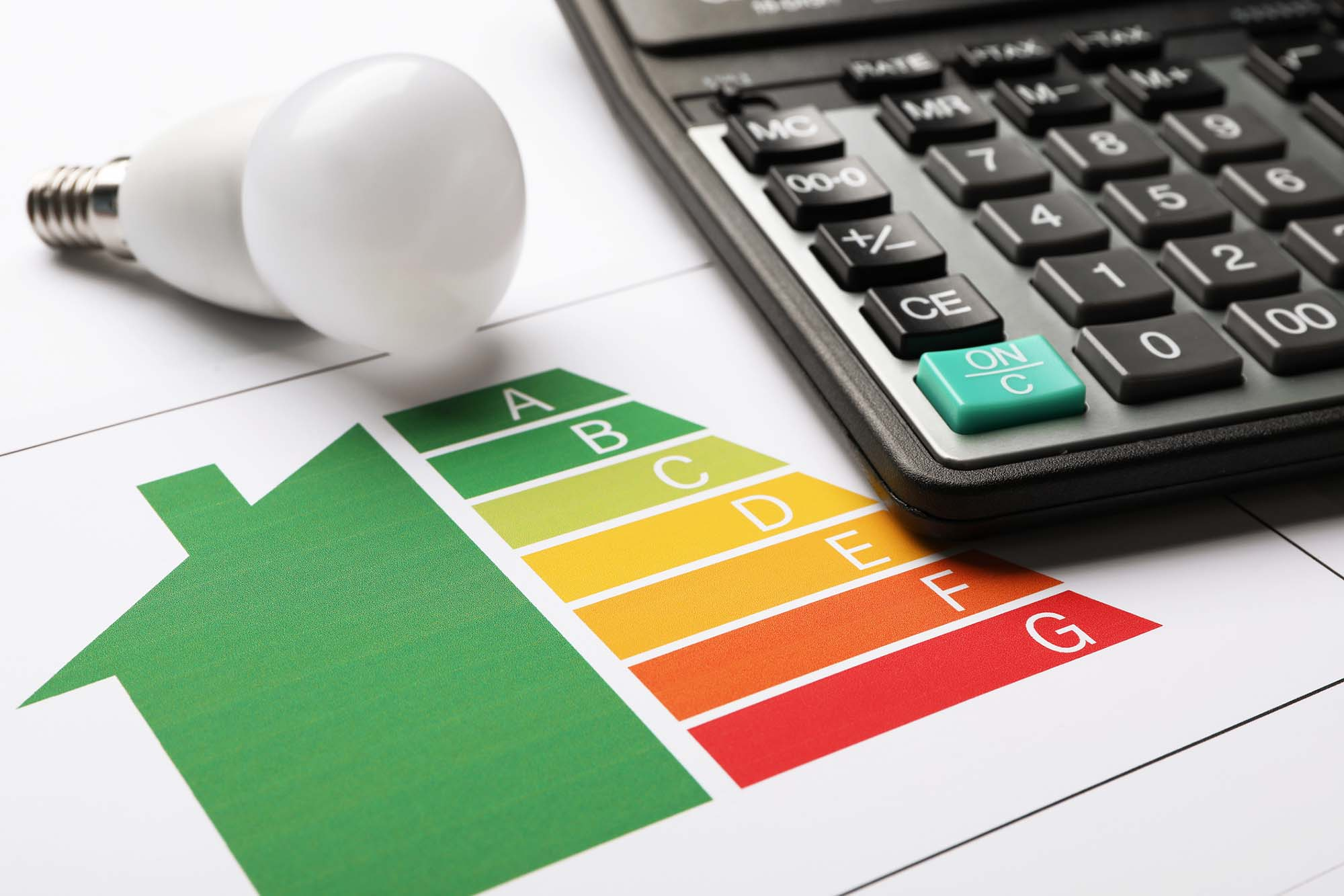 Energy efficiency rating chart, LED light bulb and calculator on